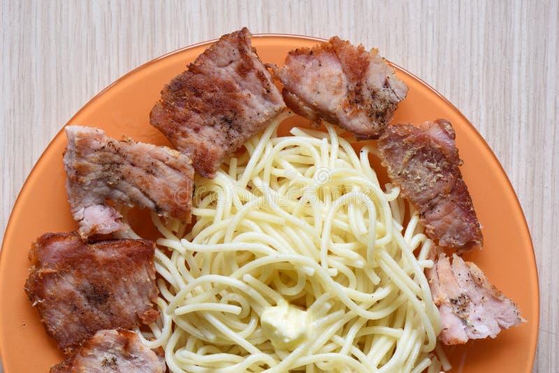 Vue supérieure d'un plat avec des pâtes et des morceaux frits de viande de porc photo libre de droits