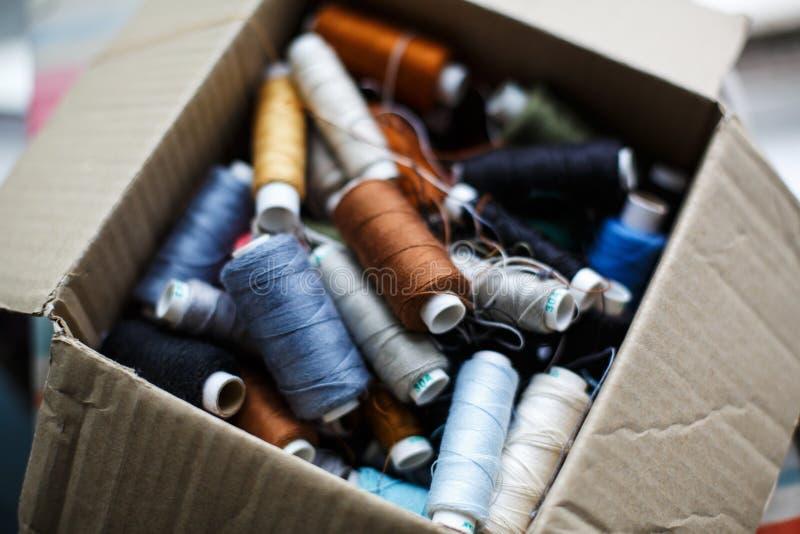 Vue supérieure d'une boîte avec des écheveaux de fil coloré Table blanche Tailleur de lieu de travail Industrie de couture photos stock