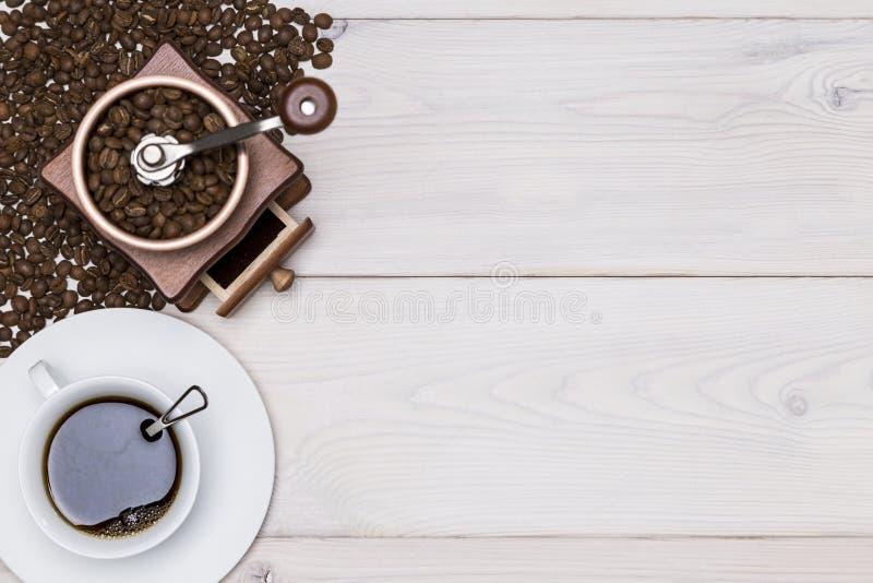 Vue supérieure d'une broyeur de café et d'une tasse se tenant dans les haricots photographie stock libre de droits