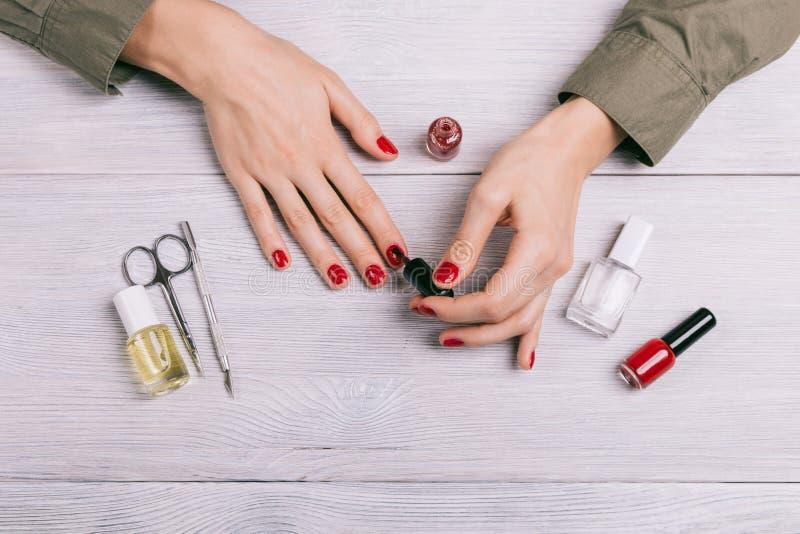 Vue supérieure d'une femme faisant des ongles d'une manucure et de peinture avec de la La rouge images stock