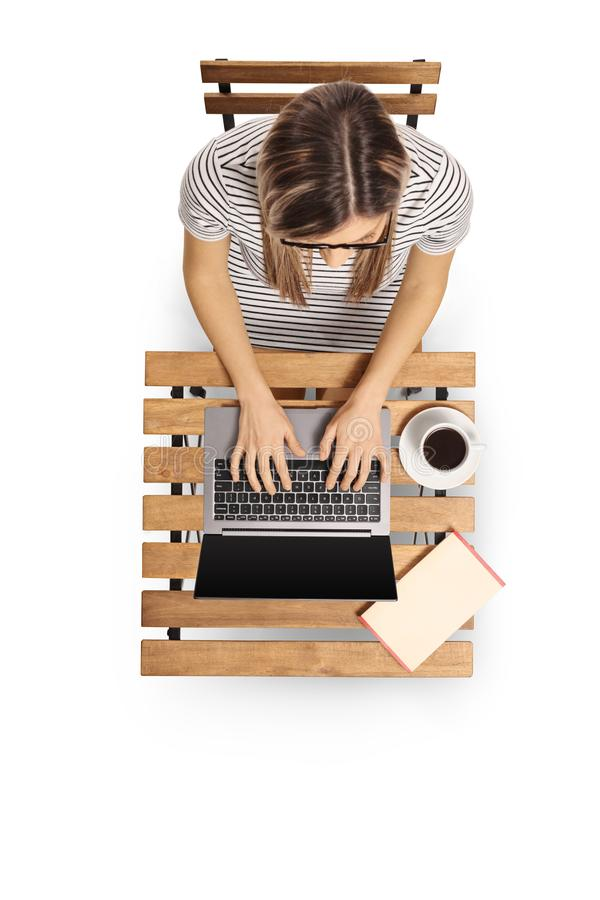Vue supérieure d'une jeune femme travaillant sur un ordinateur portable sur une table en bois images libres de droits