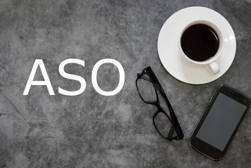 Vue supérieure d'une tasse de café, des lunettes de soleil et du téléphone portable sur le fond gris de plancher écrit avec ASO photos stock