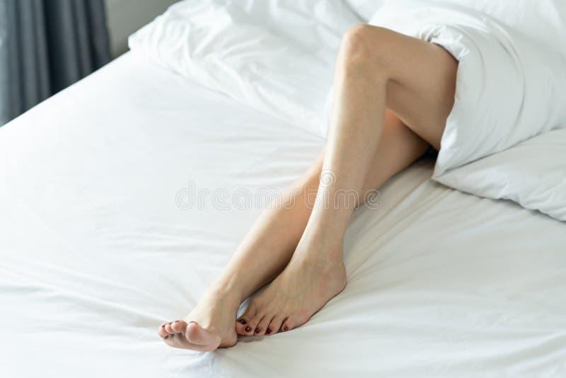 Vue supérieure de belles jambes minces d'une femme Jambes nues d'une jeune femme dormant sur son foyer mou de lit à la maison - image stock