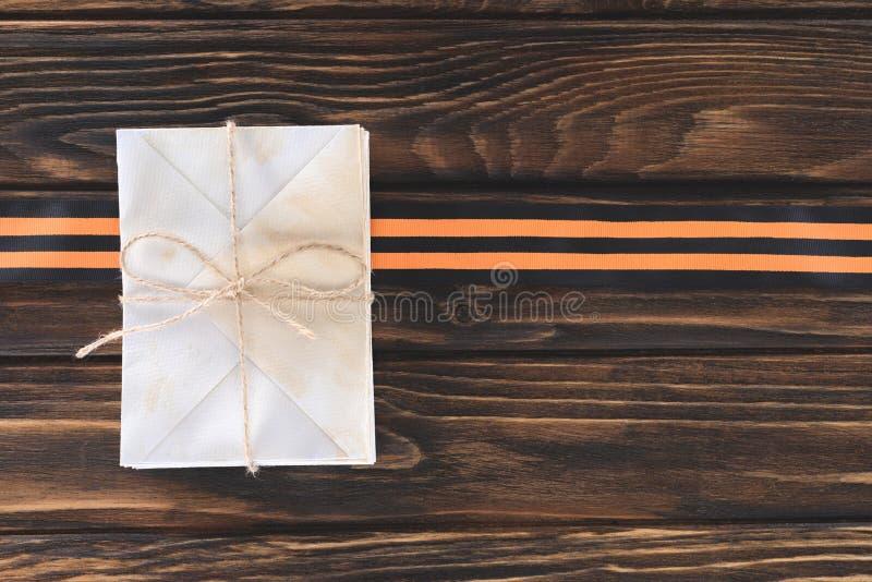 vue supérieure de boîte enveloppée par la ficelle et le ruban de St George sur les planches en bois image stock