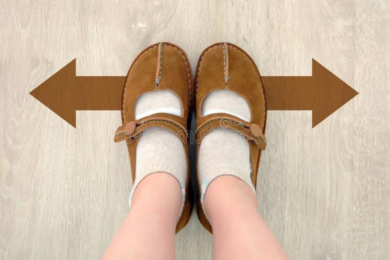 Vue supérieure de botte de Brown avec la flèche différente de décision de Brown Une paire de position de pieds Direction de march photographie stock libre de droits