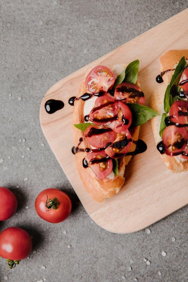 vue supérieure de bruschette délicieuse avec balsamique sur le conseil en bois et les tomates fraîches sur le gris photos libres de droits
