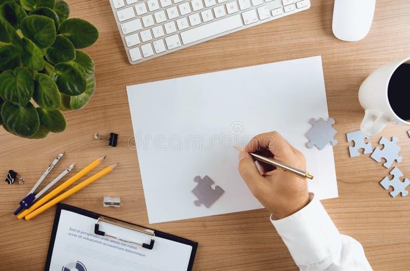 Vue supérieure de bureau avec un stylo de participation de main d'homme d'affaires image stock