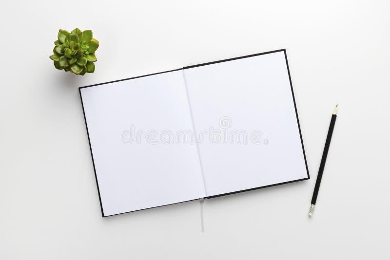 Vue supérieure de bureau blanc contemporain avec le livre et le crayon images libres de droits