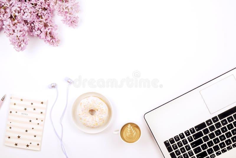 Vue supérieure de bureau de main-d'œuvre féminine avec l'ordinateur portable, les fleurs et les différents articles de fourniture photos stock