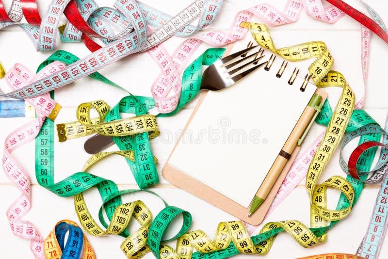 Vue supérieure de carnet avec la fourchette entourée avec les bandes de mesure colorées sur le fond en bois blanc L'espace de cop images libres de droits