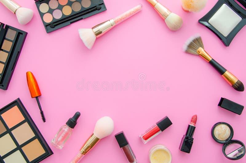 Vue supérieure de cosmétiques sur une table rose L'appartement de lieu de travail s'étendent avec des cosmétiques, le rouge à lèv images libres de droits