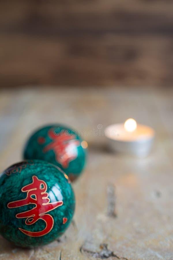 Vue supérieure de deux boules chinoises et bougie sur la table en bois superficielle par les agents et le fond foncé images stock