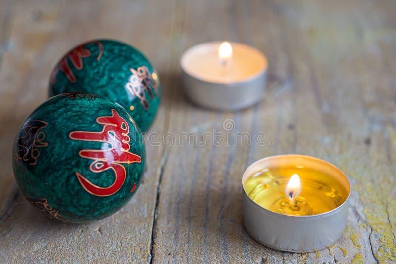 Vue supérieure de deux boules chinoises et de deux bougies sur le conseil en bois superficiel par les agents photos stock