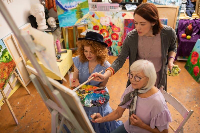 Vue supérieure de deux jeunes étudiants en art avec leur professeur âgé image libre de droits