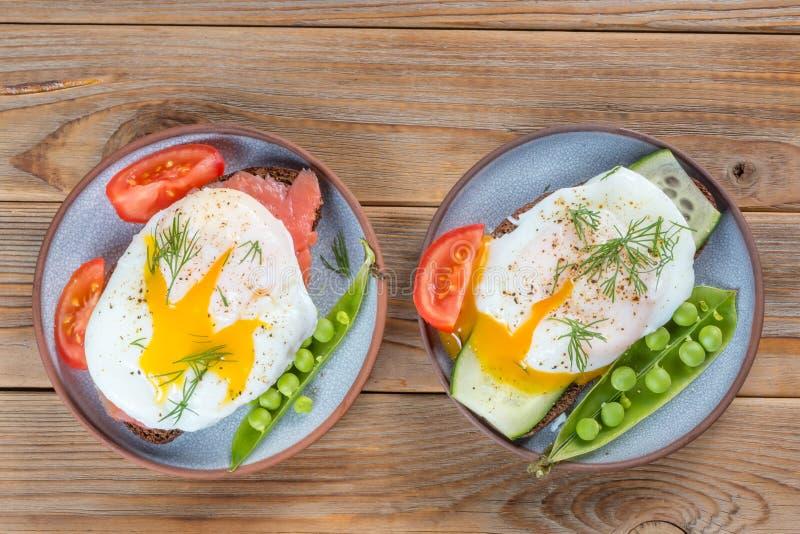 Vue supérieure de deux sandwichs avec un oeuf poché et pois et tomate d'un plat sur le fond en bois photo stock