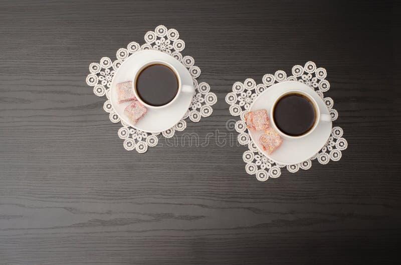 Vue supérieure de deux tasses de café sur une soucoupe avec le plaisir turc Serviettes de dentelle, table noire photo libre de droits
