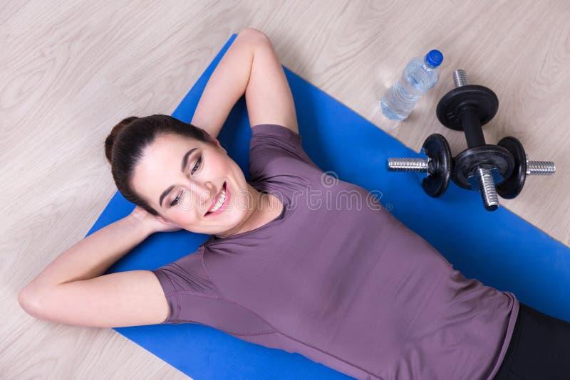 Vue supérieure de femme mince se trouvant sur le tapis de yoga après la formation images stock