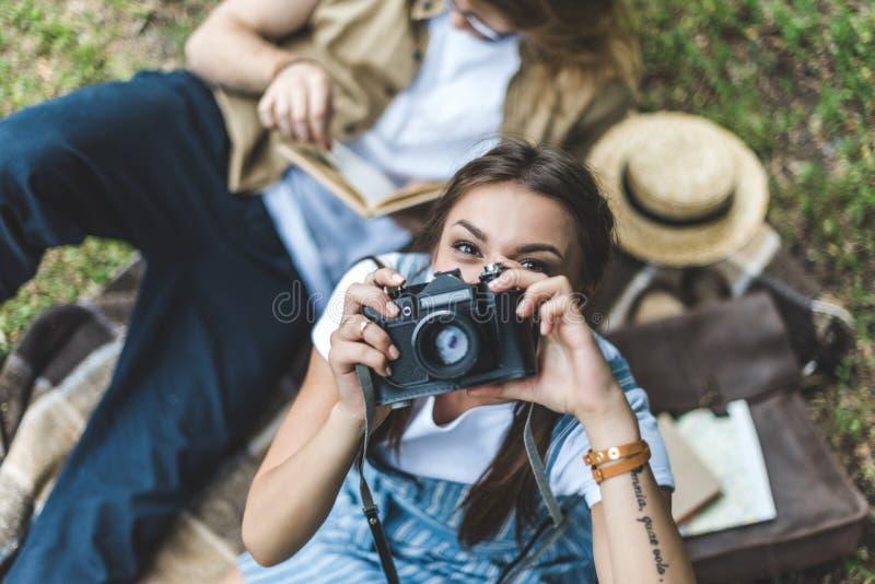 vue supérieure de femme prenant la photo avec l'appareil-photo de vintage tout en détendant en parc avec l'ami images libres de droits