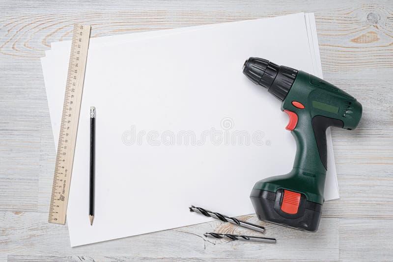 Vue supérieure de foret vert avec le peu, la règle et le crayon sur le papier blanc blanc Établi en bois de DIY, l'espace de copi photo libre de droits