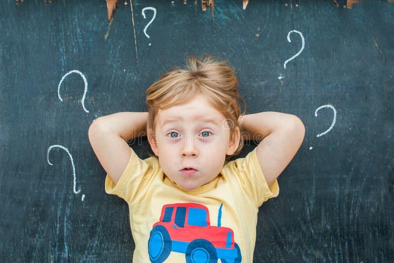 Vue supérieure de garçon blond d'enfant avec le point d'interrogation sur le tableau noir Concept pour la confusion, la séance de image libre de droits