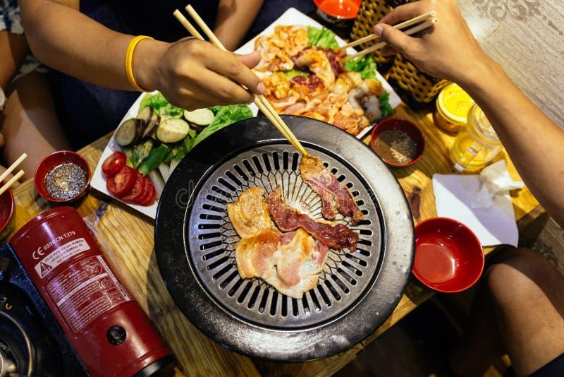 Vue supérieure de griller le porc coupé en tranches de BBQ sur la casserole chaude par la baguette au restaurant à Hanoï, Vietnam image stock