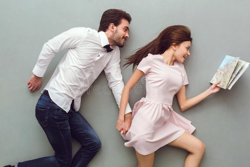 Vue supérieure de jeunes couples sur le fond gris regardant la carte images libres de droits