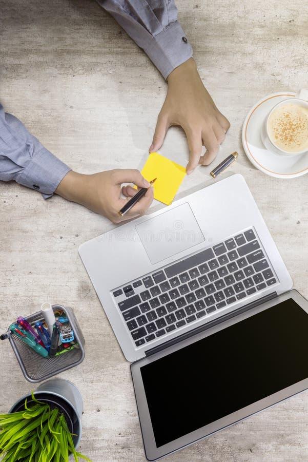 Vue supérieure de l'écriture d'homme d'affaires dans les notes collantes avec l'ordinateur portable, le café, la plante mise en p image libre de droits