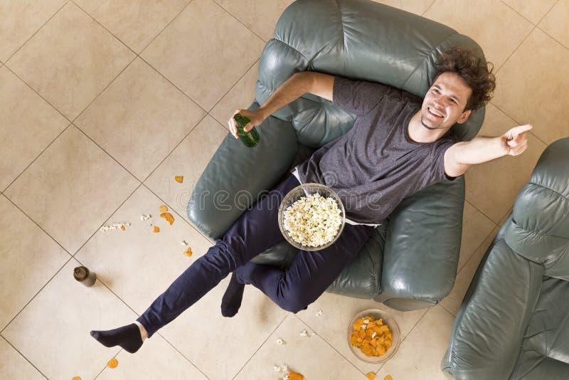 Vue supérieure de l'homme avec de la bière et des pommes chips et de maïs éclaté regardant la TV à la maison photographie stock libre de droits