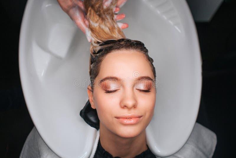 Vue supérieure de la belle jeune femme avec les yeux fermés souriant tandis que cheveux blonds de lavage de coiffeur Soins capill images libres de droits