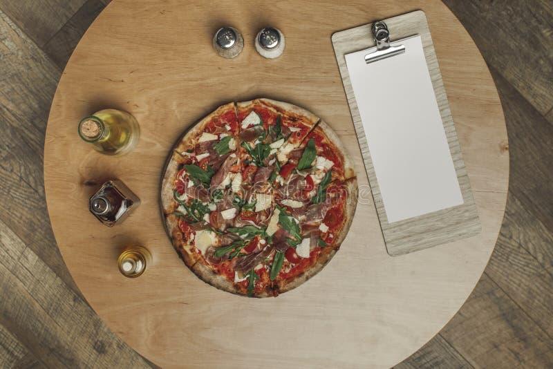 Vue supérieure de la disposition de la pizza italienne, des épices et des divers types d'huile dans des bouteilles image stock
