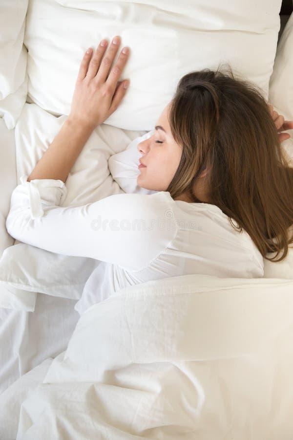 Vue supérieure de la jeune femelle calme dormant paisiblement dans le lit photo stock