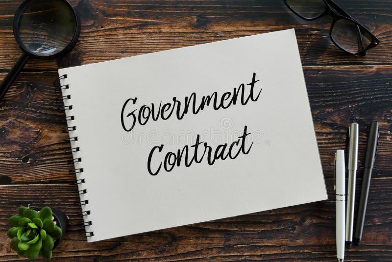 Vue supérieure de la loupe, des verres, du stylo, de l'usine et du carnet écrits avec le contrat gouvernemental photographie stock
