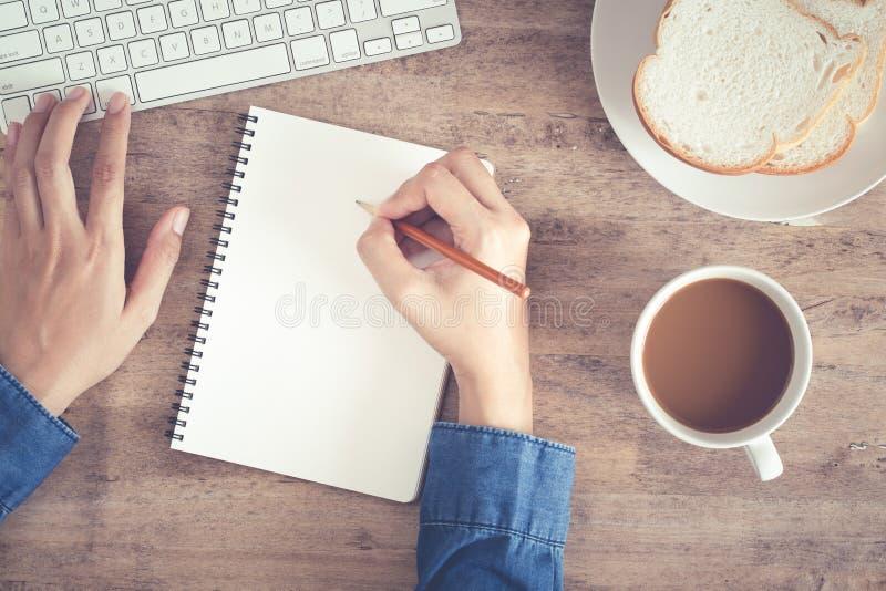 Vue supérieure de la main d'affaires de femme écrivant le carnet et à l'aide de l'ordinateur sur le bureau et avoir le café, pain photographie stock libre de droits