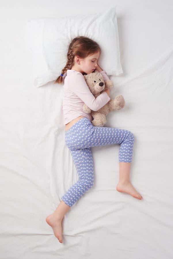 Vue supérieure de la petite fille mignonne dormant avec le nounours images libres de droits