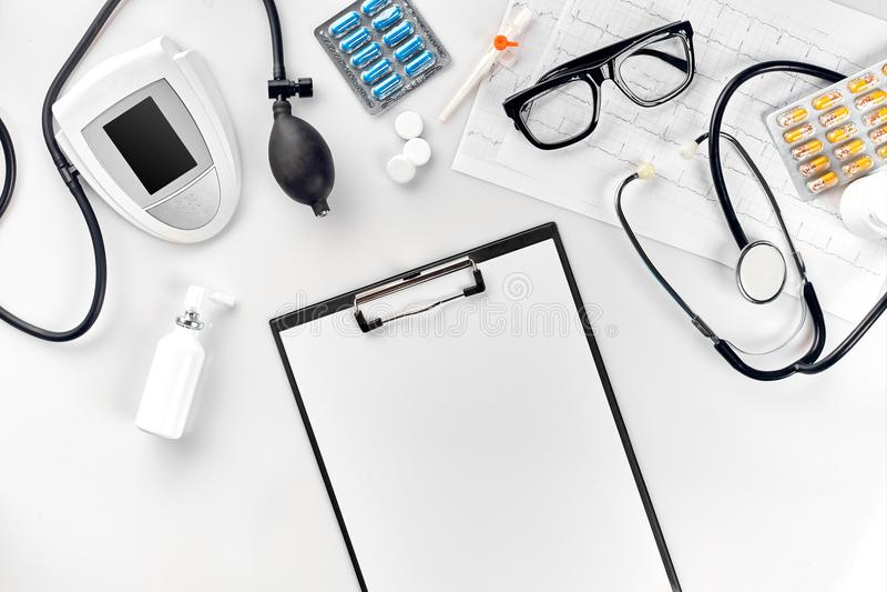 Vue supérieure de la table de bureau du ` s de docteur, papier blanc sur le presse-papiers avec le stylo, stéthoscope, manomètre  image stock