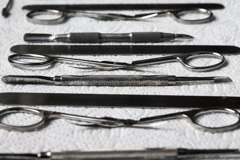 Vue supérieure de la trousse d'outils de manucure des outils métalliques sur stérilisation de serviette de papier la macro, désin image libre de droits