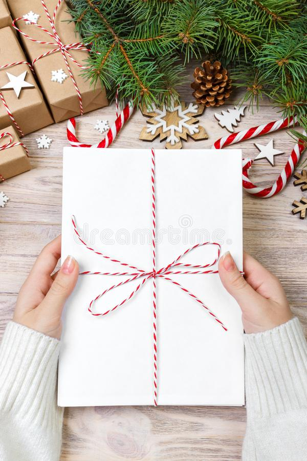 Vue supérieure de lettre de Noël à disposition Fermez-vous des mains tenant le wishlist vide sur la table en bois avec la décorat photographie stock