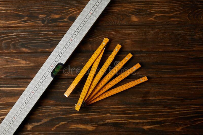 vue supérieure de niveau pliant de mètre et d'esprit sur la table en bois photo libre de droits