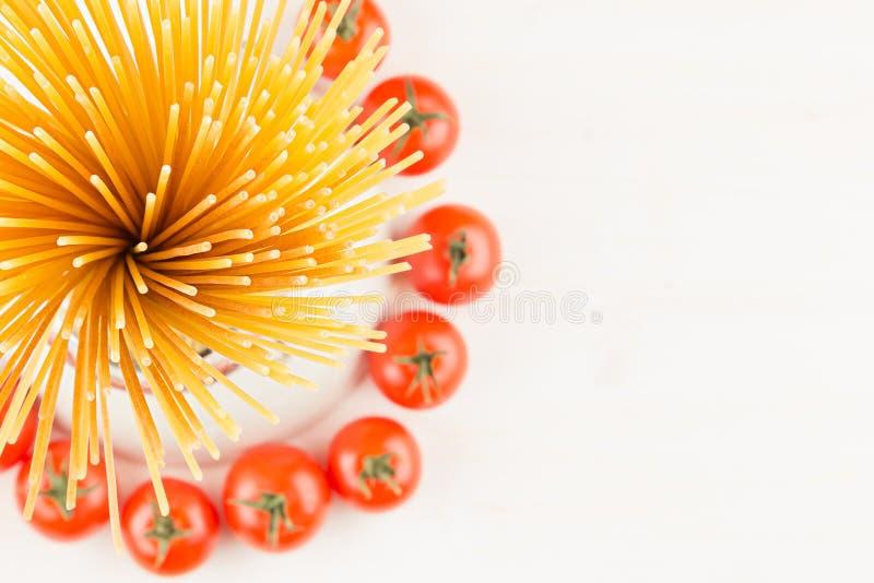 Vue supérieure de pâtes italiennes d'ingrédients - spaghetti de gerbe, tomates-cerises, basilic, fromage sur le conseil en bois b images libres de droits