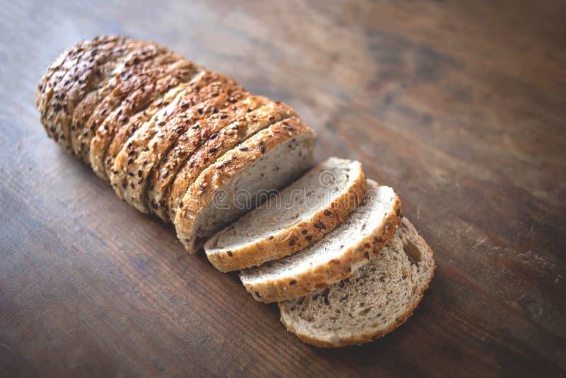 Vue supérieure de pain entier coupé en tranches sur le backg en bois ructic foncé photos libres de droits