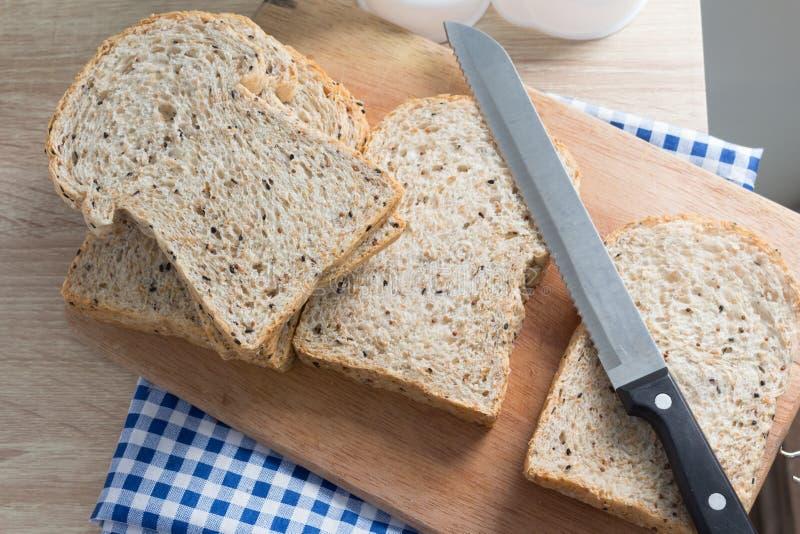 Vue supérieure de pain entier coupé en tranches sur une table en bois photographie stock
