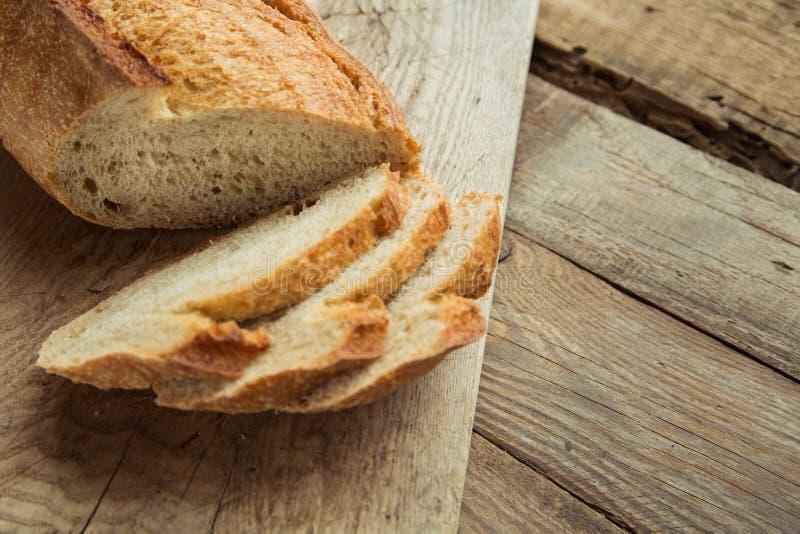 Vue supérieure de pain entier coupé en tranches sur une table en bois photos stock