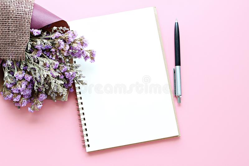 Vue supérieure de papier ouvert de carnet avec les pages vides et de bouquet des fleurs sauvages sèches sur le fond rose avec l'e photo stock