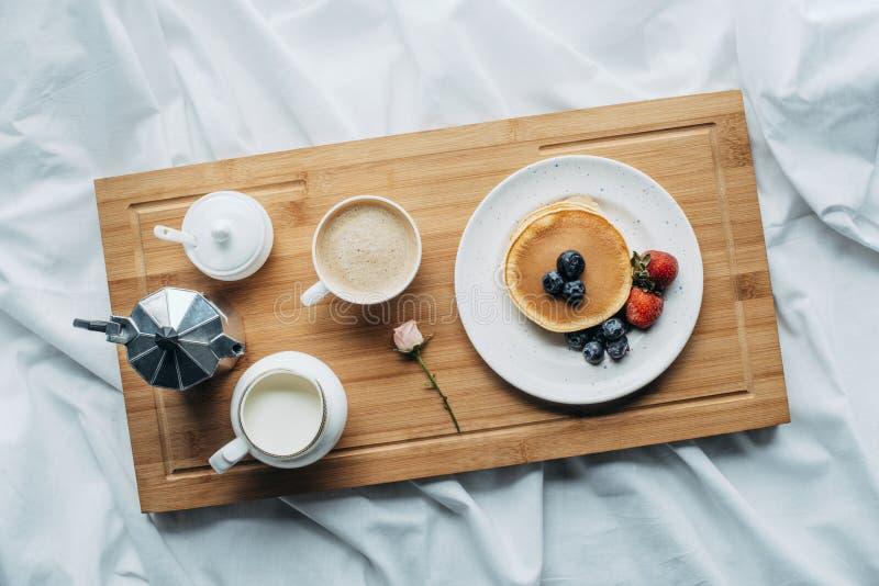 vue supérieure de petit déjeuner dans le lit avec les crêpes et le café fraîchement cuits au four image stock