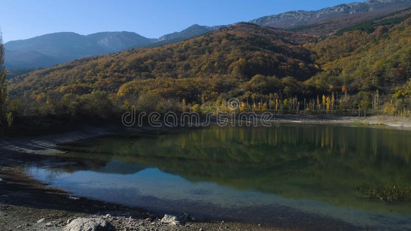 Vue supérieure de petit lac avec la réflexion des montagnes en automne projectile Belle vue avec la réflexion de coloré photographie stock libre de droits