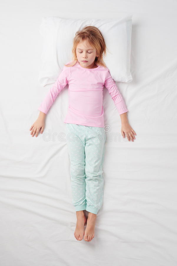 Vue supérieure de petite fille dormant dans la pose de soldat image libre de droits