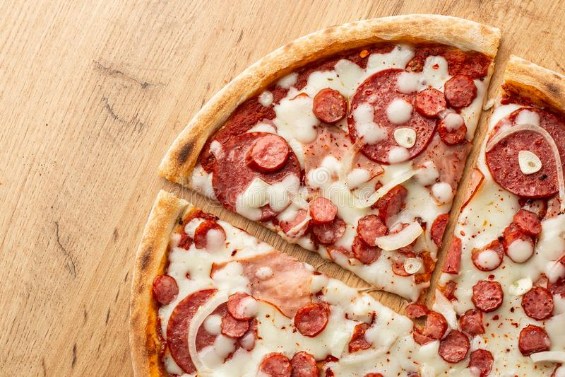 Vue supérieure de pizza avec le poivre de piment, les saucisses chaudes, l'oignon, le jambon, le salami, l'ail, les tomates et le photo stock