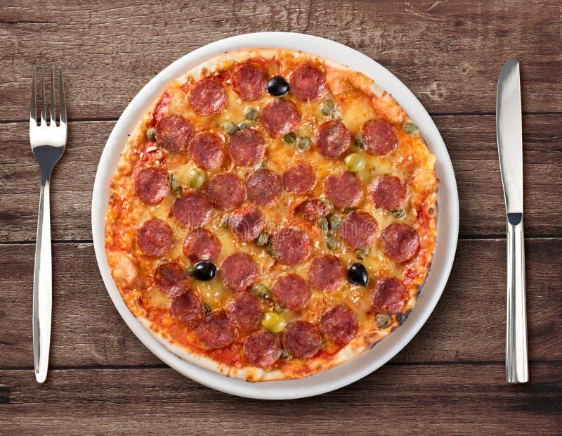 Vue supérieure de pizza de salami de plat avec la fourchette et le couteau photos stock
