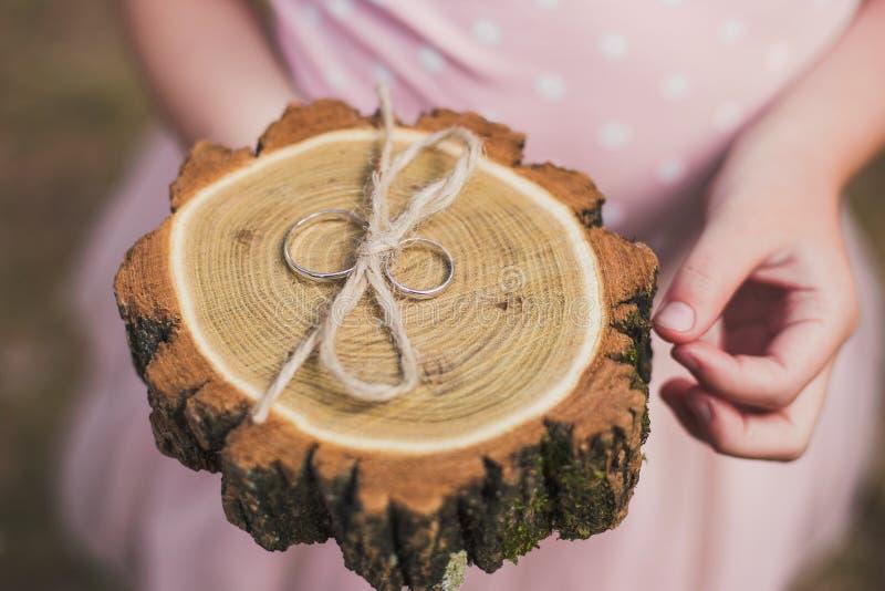 Vue supérieure de plan rapproché de deux anneaux de mariage d'or sur le fond en bois photos libres de droits