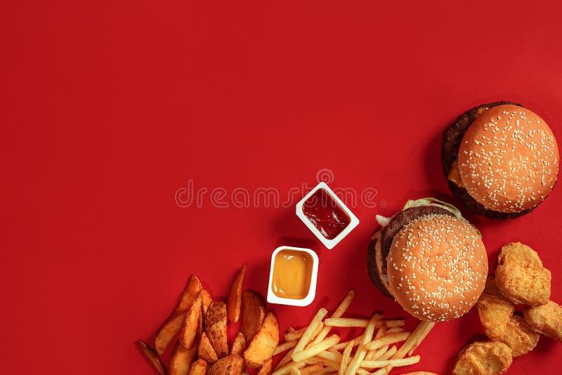Vue supérieure de plat d'aliments de préparation rapide Hamburger de viande, pommes chips et pépites sur le fond rouge Compositio photos libres de droits